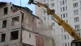 Excavator machinery working on demolition old house stock video