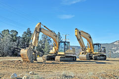 Excavator. These machines are two Caterpillar excavators used in preparing a site for construction. The excavator in the foreground has a trenching attachment Stock Images