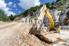 Excavator in a marble quarry Stock Images