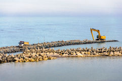 Excavator marine dam tetra pod working site Stock Photos