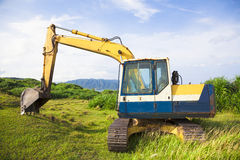 Excavator on the meadow with sky and ocean background Stock Images
