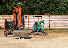An excavator and a mini excavator ready to dig into the  construction site Royalty Free Stock Photography