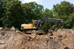 Excavator on the mound. Of soil near park Stock Images