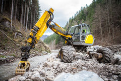 Excavator in a mountain river Royalty Free Stock Photos