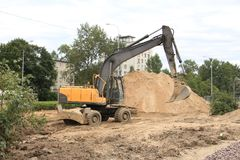 Excavator with a raised bucket. Excavator and mountain of sand Stock Photography