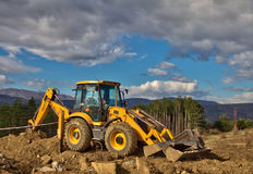 Excavator in the mountains. Yellow backhoe and cloudy sky Royalty Free Stock Photos