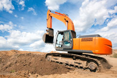 Excavator moves with raised bucket during earth moving works. Excavator machine moves with raised bucket on construction site during earth moving works Royalty Free Stock Photography