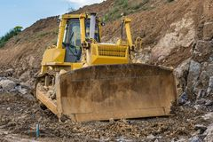 Excavator moving granite and other rocks in the construction of a road royalty free stock images