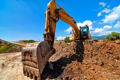 Excavator moving soil and sand on road construction site
