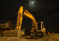 Excavator by night. An excavator by night at a construction area Stock Photos