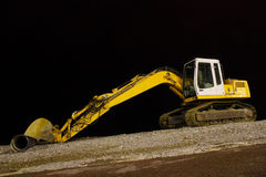 Excavator on night pebble beach. Mounting tube Stock Photo