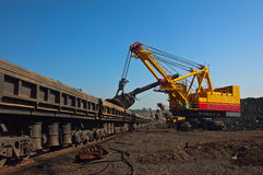 Excavator and open goods trucks. Big excavator in opencast mine load iron ore into open goods trucks on blue sky background Stock Photos
