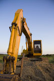Excavator overlooking farmland. Shot at sunset Stock Photography