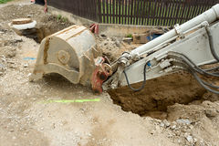 Excavator ploughshare on trench - constructing canalization Royalty Free Stock Photo