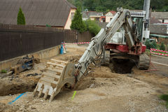 Excavator ploughshare on trench - constructing canalization Royalty Free Stock Photography