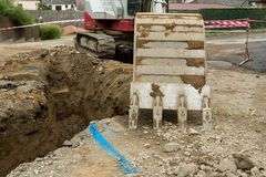 Excavator ploughshare on trench - constructing canalization Royalty Free Stock Image