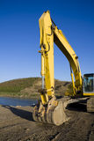 Excavator by pond. Yellow excavator working digging up natural area with pond and hill in the background Stock Photo