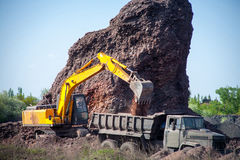 Excavator poured cargo into the body of a quarry truck for transportation to the construction site Royalty Free Stock Photo