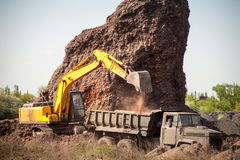 Excavator poured cargo into the body of a quarry truck for transportation to the construction site Stock Image