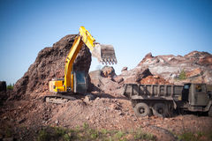Excavator poured cargo into the body of a quarry truck for transportation to the construction site Stock Photo