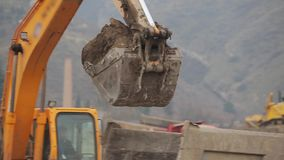 Excavator pours sand into a truck. Close-up of excavator pouring sand into a truck on quarry stock video