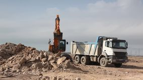 Excavator pours sand into a truck. Wide shot of excavator pouring sand into a truck on quarry stock video footage