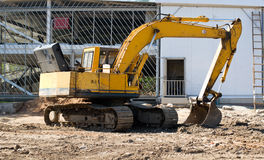 Excavator on project site. Big yellow excavator on project site in a sunny day Stock Photos