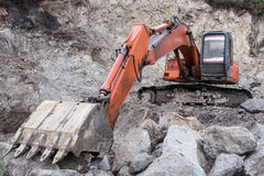 Excavator in quarry. Red Excavator surrounded by rocks in the limestone quarry stock image