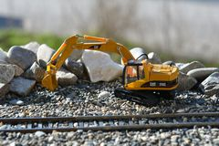 Excavator on the railroad model Stock Photos