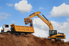 Excavator and rear-end tipper royalty free stock image