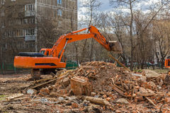 Excavator removes construction waste after building demolition Royalty Free Stock Image