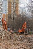 Excavator removes construction waste after building demolition Stock Image
