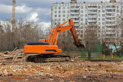 Excavator removes construction waste after building demolition Royalty Free Stock Images