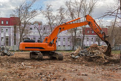 Excavator removes construction waste after building demolition Stock Images