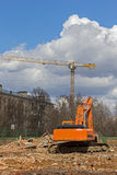 Excavator removes construction waste after building demolition Stock Photo