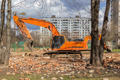Excavator removes construction waste after building demolition Royalty Free Stock Photo