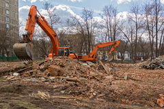 Excavator removes construction waste after building demolition Stock Photos