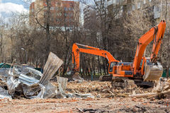 Excavator removes construction waste after building demolition f Royalty Free Stock Images