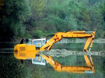 Excavator in the River Stock Images