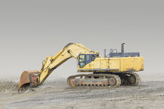 Excavator in rocky ambiance. Tracked yellow excavator in rocky quarry ambiance Stock Photo