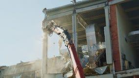 Excavator ruins column of dangerous hockey arena building