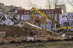 Excavator and ruins of the old brick building Royalty Free Stock Image