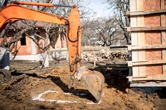 Excavator scoop on construction site, digging and loading dumper trucks. Royalty Free Stock Photos