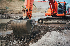 Excavator scoop in dirt, working on highway construction and building foundation Stock Photo