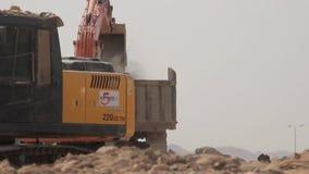 Excavator scoop loads a dump truck. Madina - Saudi Arabia 8 December 2014 - Excavator scoop loads a dump truck stock video