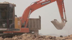 Excavator scoop loads a dump truck. Madina - Saudi Arabia 8 December 2014 - Excavator scoop loads a dump truck stock video footage