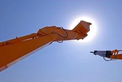 Excavator scoop in sky and sun Stock Photos