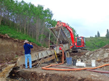 An excavator screening pay dirt at a gold claim in northern bc Stock Image