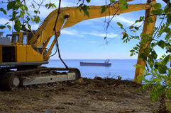 Excavator on seaside construction site Stock Photo