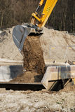 Excavator shovel. An excavator shovel full of sand putting it on a lorry stock image